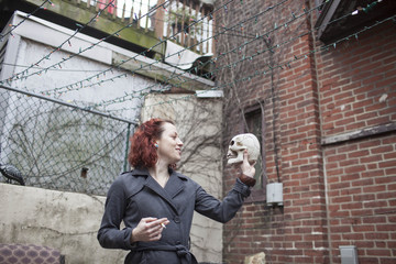 Young woman smoking cigarette while holding skull in hand