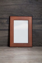 blank frame poster on the wooden table