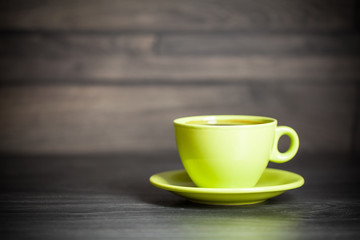 Green cup of hot tea on wood background with leaf. Autumn.