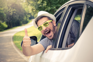 Young man wearing hat and sunglasses showing thumbs up from driver's seat through opened window. Vacation and travel concepts.  Wall mural