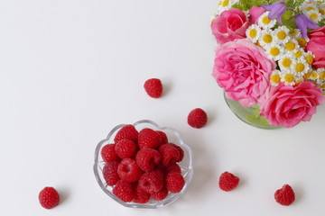 Raspberries in a bowl on a white table and bouquet of roses and daisy flowers in a vase. High angle view. Decorative corner frame or border with red raspberry fruits and flowers on white background.