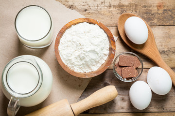 ingredients for making pancakes or cake - flour, egg, butter, milk, chocolate on the old wooden background. top view. rustic or rural style. background with free text space. Ingredients for the dough