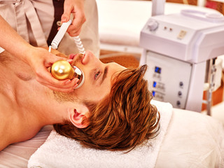 Young woman luxuriating on electroporation facial therapy at beauty salon.