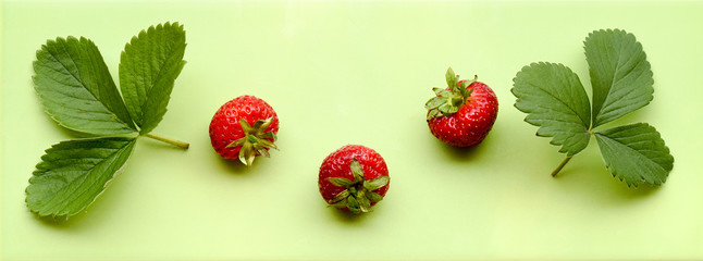 Strawberries with leaves on a green background