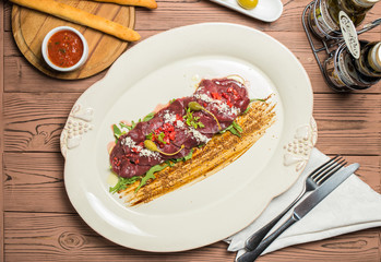 carpaccio with deer served on white plate