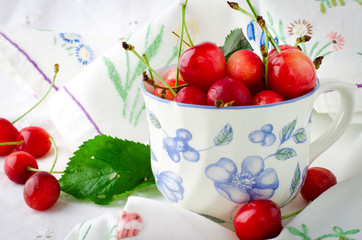 Sweet ripe fresh cherry berries with green leaves in cup