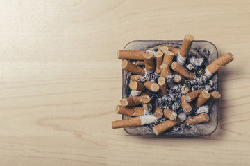 Many butts on a small glass ashtray