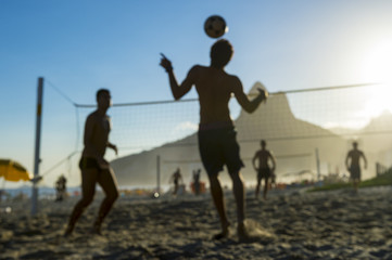 Defocused scene of silhouettes of Brazilians playing futevolei (footvolley) against a sunset backdrop of Dois Irmaos Two Brothers Mountain on Ipanema Beach, Rio de Janeiro, Brazil