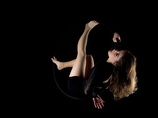 Graceful aerial dancer woman isolated on black