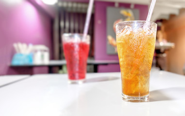 Lemon tea Thai herbal drinks with ice in glasses on the blurred cafe background.