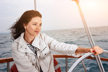 young woman with steering wheel on a yacht