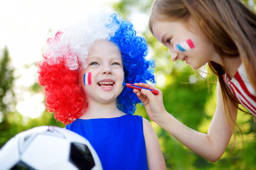 Two funny little sisters supporting and cheering their national football team