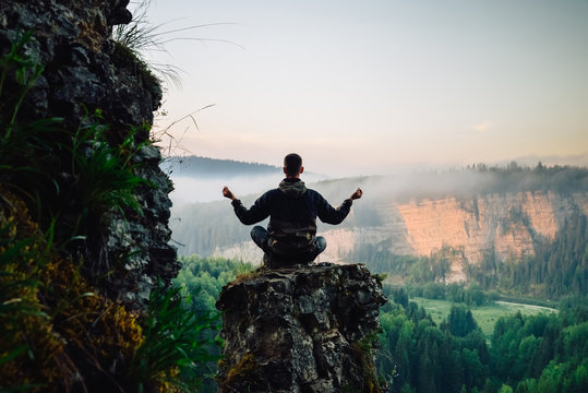Man sitting on the top of the mountain in yoga pose