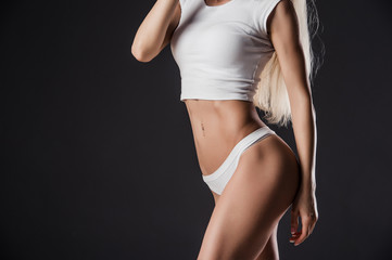 Waistline of a beautiful young healthy woman, isolated on black background