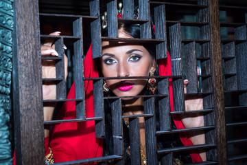 eyes beautiful Arab woman in red, peeping from behind a wooden lattice ornamental