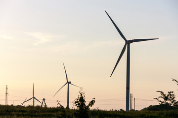 Wind turbines generating electricity on background of sky