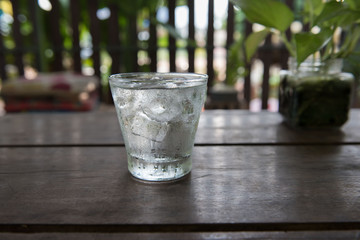 Cold water in a glass on a wooden table.