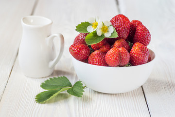 Appetizing strawberry in the bowl. White rustic table