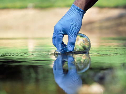 Water sample. Hand in glove collects water to explore. Concept - water purity analysis, environment, ecology. Water testing for infections, permission to swim