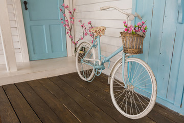 white and blue vintage bicycle with flowers in a basket