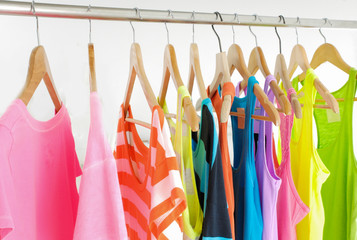 different female shirts on wooden hangers