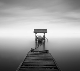 disconnected - A abandoned jetty on a beach in black and white.