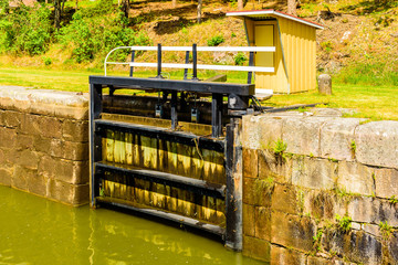 Open canal lock with a small control shed behind.