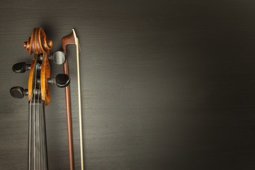 Old violin on dark wooden table. Detail of old violin on a black background. Invitation to the Violin Concerto.