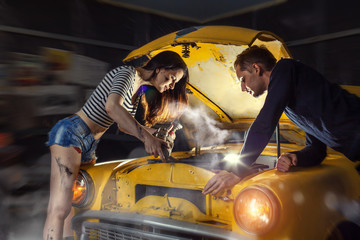 Woman mechanic in sexy shirts is repairing an old car. Car owner