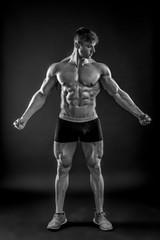 Muscular bodybuilder guy doing posing over black background