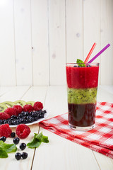 Berry smoothie.Fresh summer cocktail.Blueberry,raspberry,kiwi.Vitamin A. Vitamin C.Checkered napkin.On white wooden table with ingredients.Healthy lifestyle.Diet and weight loss concept.