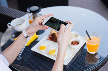 Woman hands taking food photo by mobile phone. Food photography. Delicious breakfast.