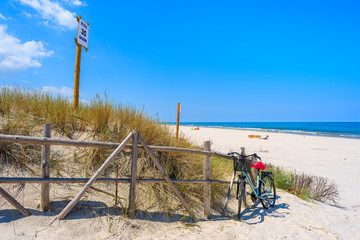 Fototapete - Bike parked at entrance to idyllic sandy beach in Bialogora coastal village, Baltic Sea, Poland. Sign on wooden pole states