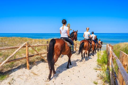 Young women riding horses to sandy beach in Lubiatowo coastal village, Baltic Sea, Poland