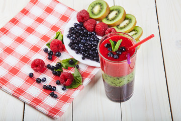 Berry smoothie.Fresh summer cocktail.Blueberry,raspberry,kiwi.Vitamin A. Vitamin C.Checkered napkin.On white wooden table with ingredients.Healthy lifestyle.Diet and weight loss concept.Top view