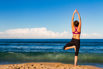 Young woman makes Yoga on a Beach