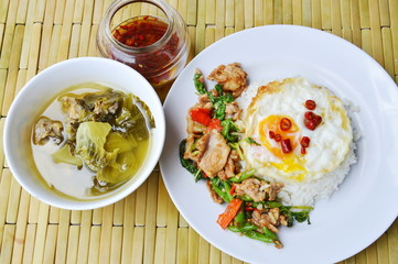 spicy stir fried pork and basil leaf on rice eat with pickled cabbage soup