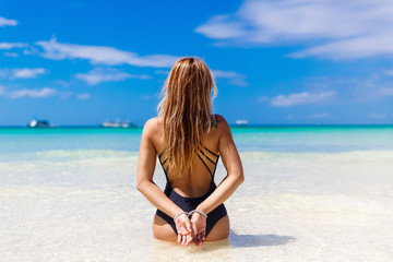 Happy beautiful young girl back to the viewer on tropical beach