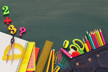 Back to school concept. School supplies on empty blackboard