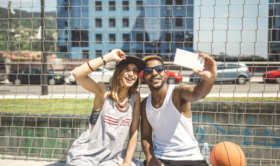 Young couple taking selfie at basketball court