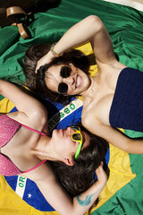 Two friends wearing beachwear, lying on Brazilian flag