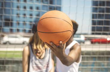 Young couple hiding faces behind basketball