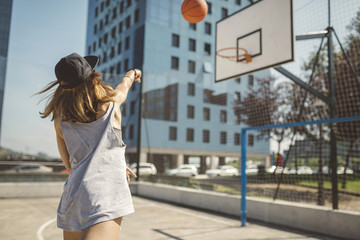 Young woman aiming at basketball hoop