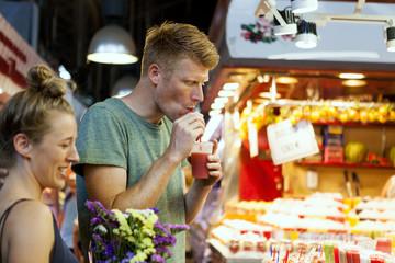 Man drinking smoothie on a street market
