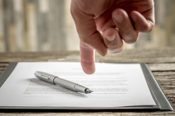 Man pointing to a document with a pen