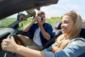 man photographing woman driving car by film camera