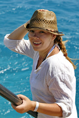 portrait of a smiling young woman in a straw hat on the sea