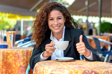 Happy young woman enjoying a cup of coffee