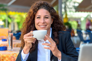 Exultant young woman enjoying a cup of coffee