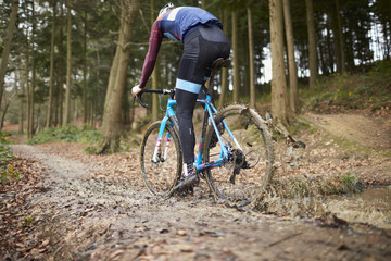 Cross-country cyclist riding in mud, low angle back view